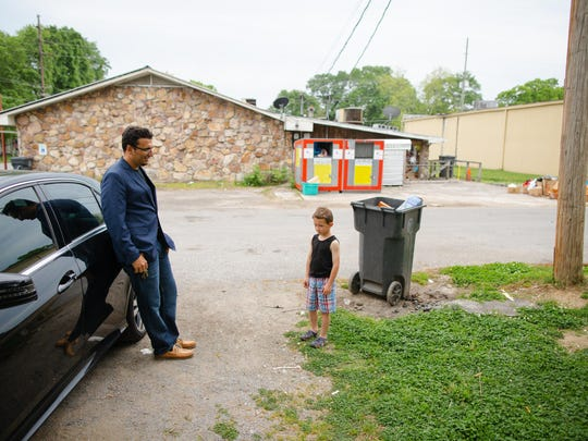 Heval Kelli leans against his sedan as he chats with C.J. Buckley, who at age 4 attended a Klan rally with his father.
