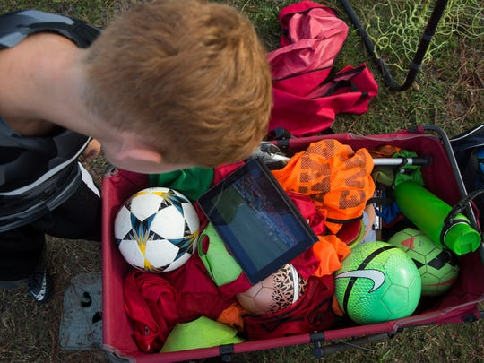 Nicholas Mazzarella, age 10, watches a live soccer match on an iPad during Kick-Off Soccer's summer day camp at the Seagate Park in Naples Friday, June 15, 2018.