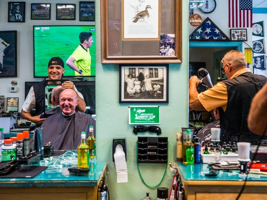 Andrew Johns works on a customer's hair at the Naples Park Barber Shop on Friday, June 15, 2018. Johns' father, Bob, owns the shop and says Johns used to cut his friends' hair when he was young.