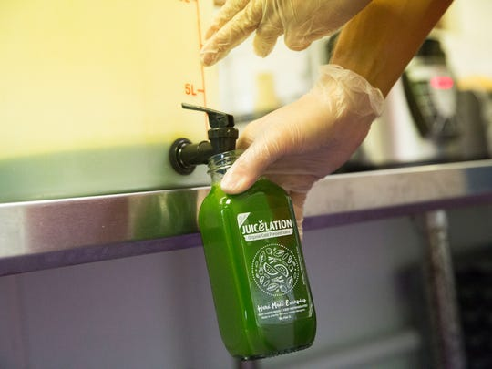 Ryan Perez pours freshly made juice into a bottle after