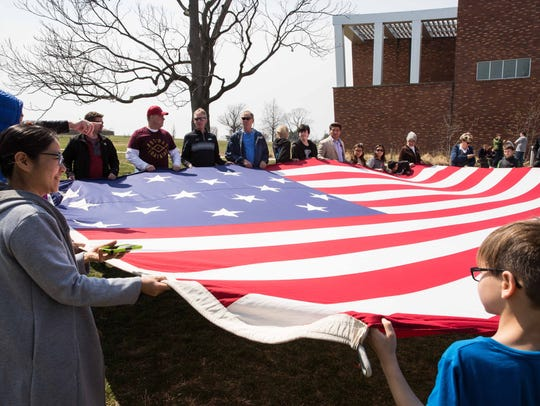 Visitors hold a 15-star American Flag at Fort McHenry