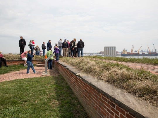Visitors stand along the wall of Fort McHenry looking