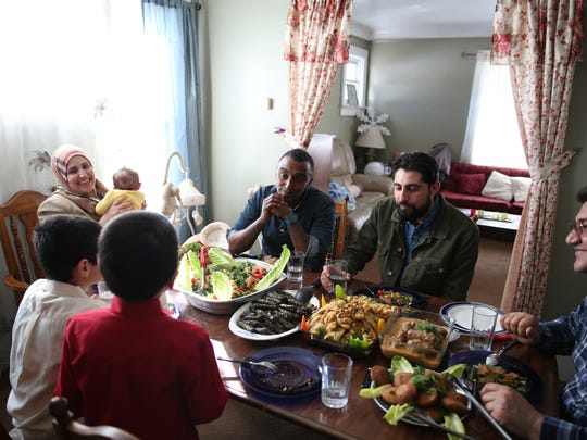 Marcus Samuelsson sits for a meal with a Syrian refugee family in Dearborn. Samuelsson is sitting next to Salwan Georges, a former Detroit Free Press photojournalist who now works at The Washington Post.
