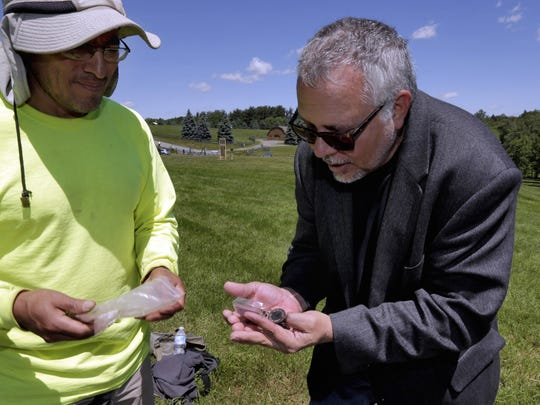 Wade Lawrence, right, museum director and senior curator at The Museum at Bethel Woods, looks at artifacts recovered from a dig at the site of the original Woodstock Music and Art Fair, in Bethel on June 14. Edgar Alarcon of the Public Archaeology Facility at Binghamton University looks on at left.