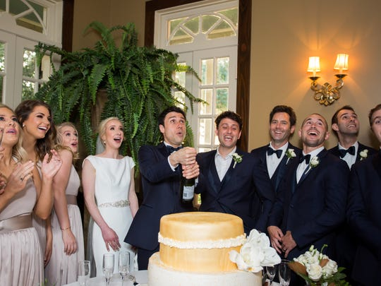 The wedding party celebrates with a cake was made by Cannatas in Houma.