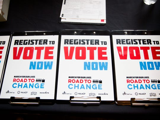 Clipboards with registration information sit on the table at Silverspot Cinema in North Naples on Monday, June 25, 2018 during the the first leg of their Florida bus tour to campaign for gun reform and register voters.