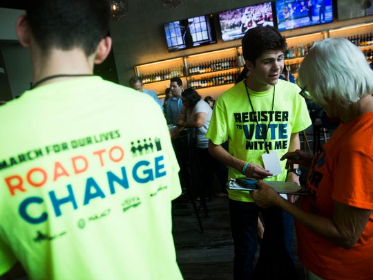 "Marjory Stoneman Douglas student Daniel Duff, 15, helps Marcia Hawken, Naples resident, register to vote during the the first leg of their Florida bus tour to campaign for gun reform and register voters at Silverspot Cinema in North Naples on Monday, June 25, 2018. ""I'm supporting these kids,"" Hawken said, ""They're our future."""