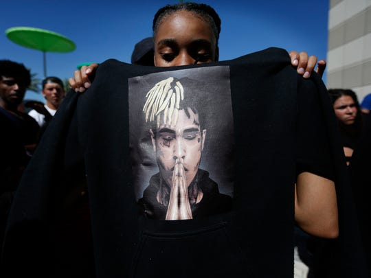 Anneyah Lawson, 14, of St. Petersburg, Fla., holds up a sweatshirt with an image of slain rapper XXXTentacion at his memorial on June 27, 2018, in Sunrise, Fla.