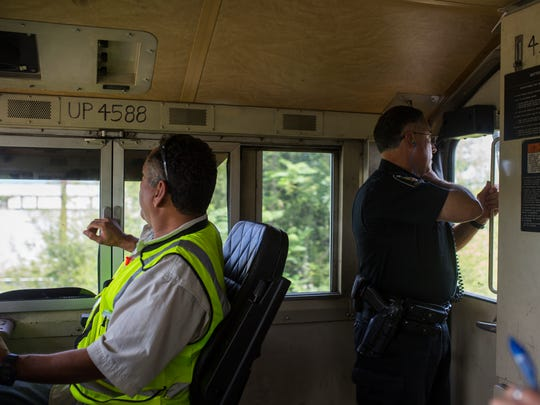 Union Pacific Special Agent Alfredo Rodriguez peers out the window of a locomotive looking for people crossing the tracks illegally as he radios to Kleberg County Sheriff deputies during a safety operation on Wednesday, June 28, 2018 in Riviera.