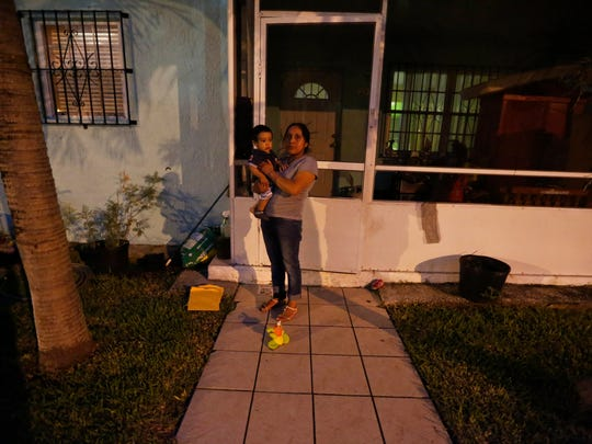 "Buena Ventura Martin-Godinez, from Guatemala, holds her son, Pedro, in front of her home in Homestead, Fla., on Wednesday, June 27, 2018. ""What I want is that they bring me my daughter and let my husband go,"" she said. ""I ask God for an opportunity to live here with my family together."""