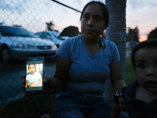 "Sitting with her son, Pedro, Buena Ventura Martin-Godinez, from Guatemala, shows a photograph of her daughter, Janne, on her phone during an interview with the Associated Press outside her home in Homestead, Fla., on Wednesday, June 27, 2018. Janne was placed in Michigan after crossing the U.S. border with her father. ""Every time she calls, she cries. I tell her we never should have come here,"" Martin said as she cradled 10-month-old Pedro in the front yard of her in-laws' house as the sun went down Wednesday. ""I never thought it would be like this."""