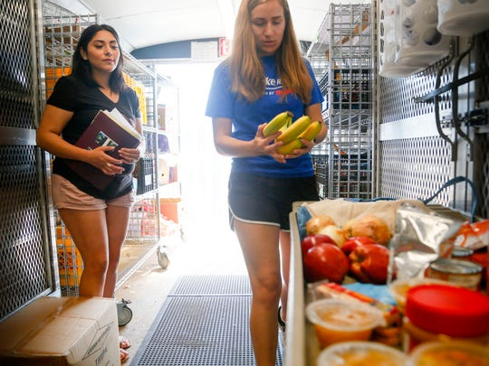 Maria Reyes of Des Moines, left, selects food for herself