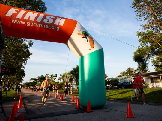 Joshua Wagner, 19, finishes first as other runners finish their first lap during the Moe's Firecracker 5k on July 4, 2018 at Fleischmann Park in Naples.