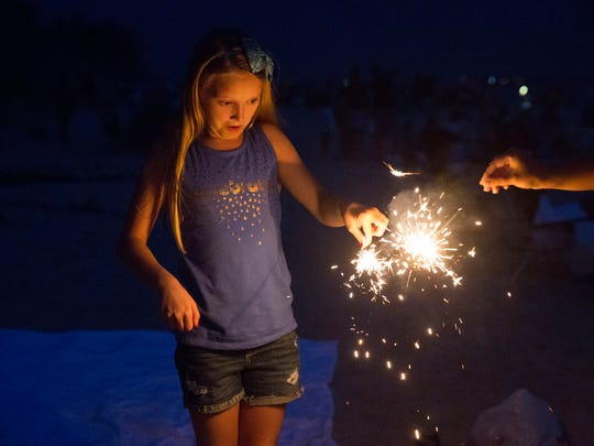 Kennedy Wagner, age 10, lights sparklers with her family before the firework presentation begins along the beach in Naples, Florida on Wednesday, July 4, 2018.