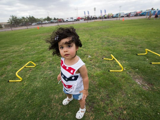 Seleni Max Herrera, 1, with wind blowing through her hair, takes a break after running through the activities area at the Sisbarro Community Park at New Mexico State University, Wednesday July 4, 2018 before the start of the Las Cruces Fourth of July Celebration.
