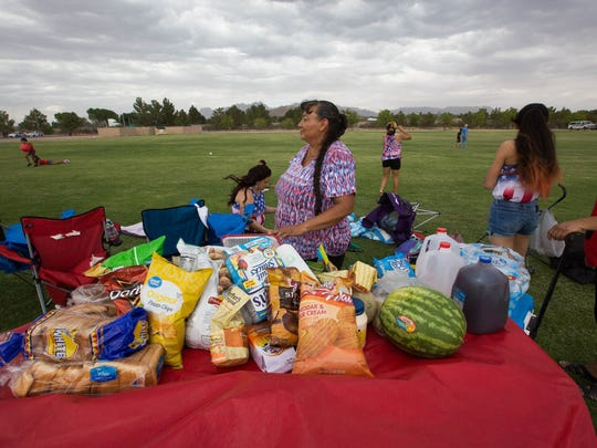 Carmen Gonzales keeps an eye on the food her family brought as wind gusts start to blow across the Sisbarro Community Park at New Mexico State University before the start of the Las Cruces Fourth of July Celebration, Wednesday July 4, 2018.