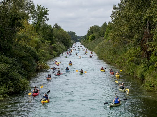 Hundreds of kayakers make their way up the Black River