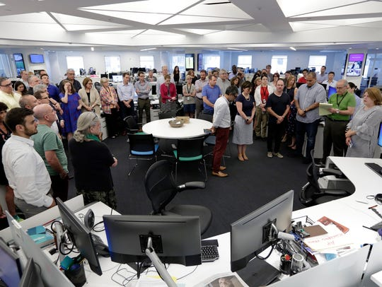 Employees gather in the newsroom of the New York headquarters
