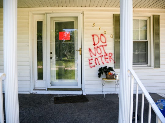 A sign marks a flood damaged home as unsafe to enter