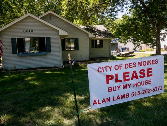 A sign asks the city to buy a flood damaged home on