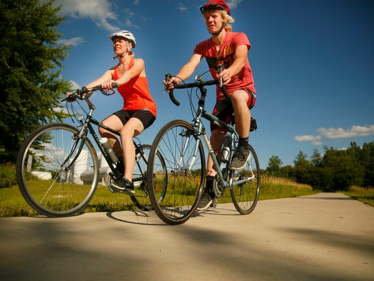 Siblings Hannah and Issac Harken ride on a bike trail
