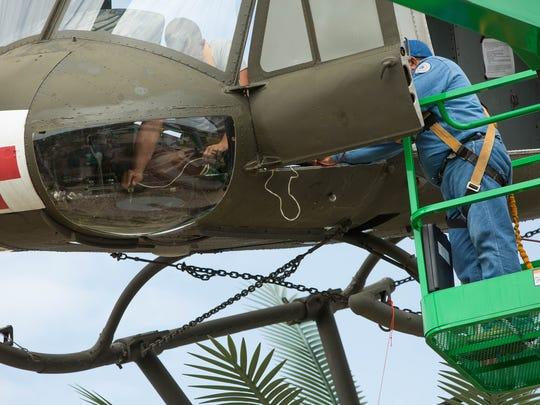George W. Hayduke, left, uses a soldering iron to put a drainage hole into the chin bubble of the Bell UH-1 Iroquois helicopter at Veterans Memorial Park, Friday July 27, 2018. Richard Pastran, right, and Hector Rodriguez, not pictured, from the Las Cruces Parks and Recreation Department, also help put the finishing touches on the repair of the helicopter, which was damaged by vandals in May.