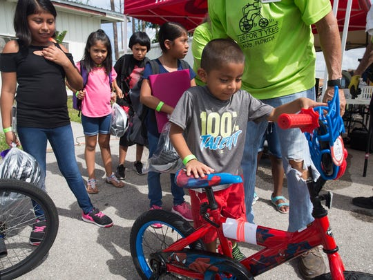 Alex Bautista, 4, tries out a Spider-Man tricycle at the third annual Christmas in July event at the Florida Sports Park, hosted by Kiwanis Florida Division 22 on Saturday, July 28, 2018. Kiwanis members provided new backpacks stuffed with clothing, school supplies and personal care items for over 2,500 homeless or at-risk of being homeless students in Collier County.