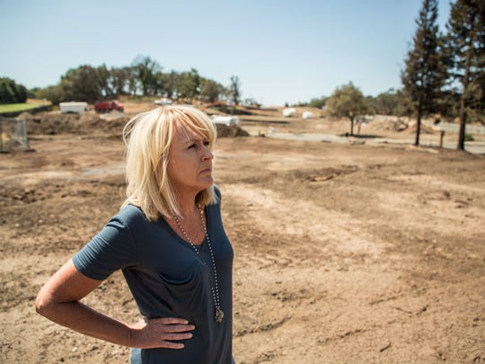 Lifelong Santa Rosa resident Paula Lindsay, 56, who lost her home in the 2017 wildfire, stands in a lot at the Oaks at Fountaingrove development that was destroyed in the 2017 fire. {ED: This is NOT her lot.