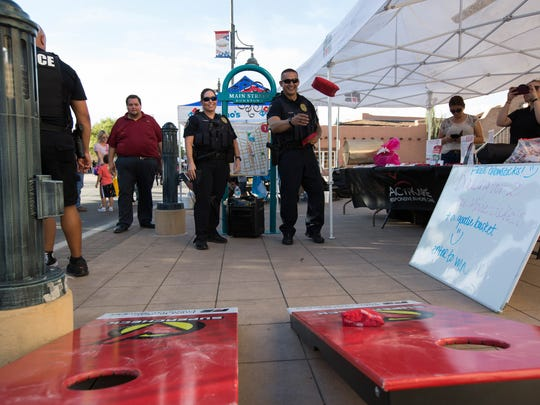 Lucy Lucero, left, and Daniel Lopez, right, both Las Cruces Police Officers play corn hole at one of the many booths set up along Main Street during a National Night Out event, Las Cruces Police and Fire Departments hosted a National Night Out event, Tuesday August 7, 2018. The event had booths from different state, local and national law enforcement agencies.