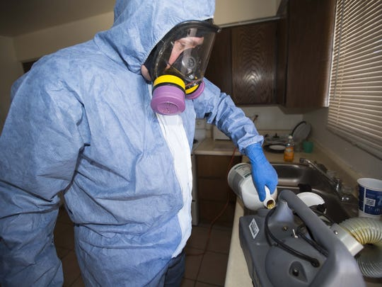 Jeffrey Lowman/The Republic Dale Cillian, owner of Biohazard Cleanup Company uses chemicals to fog a Glendale residence believed to be contaminated with Methicillin-resistant Staphylococcus aureus, or MRSA, Wednesday, November 12th, 2014, in Glendale, Ariz. Cillian used a chemical that would also be used to clean areas contaminated with viruses such as Ebola.