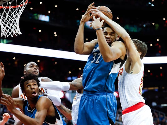 Minnesota Timberwolves center Karl-Anthony Towns (32) and Atlanta Hawks guard Kyle Korver (26) battle for a rebound as Minnesota forward Andrew Wiggins (22) looks on at left in the second half of an NBA basketball game Wednesday, Dec. 21, 2016, in Atlanta. Minnesota won 92-84. (AP Photo/John Bazemore)