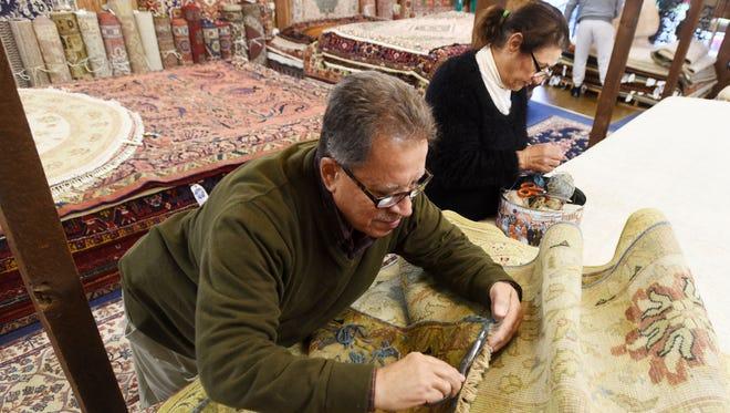 Hani Kaskas with his wife Samira Kaskas repairs a rug at his business Ark-La-Tex Oriental Rugs.