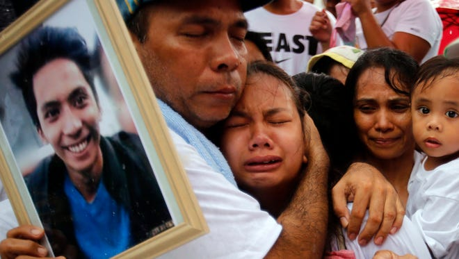 Filipino relatives mourn for Ephraim Escudero, who was a victim of extra judicial killing, during burial rites at a cemetery in San Pedro, Philippines on Sept. 30,  2017. More than half the Filipinos surveyed in a poll released by the firm Social Weather Stations (SWS) believed the country's police have been carrying out extrajudicial killings as part of President Rodrigo Duterte's war on drugs, a campaign that has killed more than 7,000 people so far. Since Duterte came to power on June 20, 2016, his aggressive war on drugs has seen more than 3,800 alleged drug traffickers and addicts killed in police operations, apart from a bigger number who were killed by vigilante groups. International organizations like Human Rights Watch have repeatedly criticized Duterte's anti-drug campaign for its various human rights violations, although the campaign and Duterte enjoys popular support in the country.