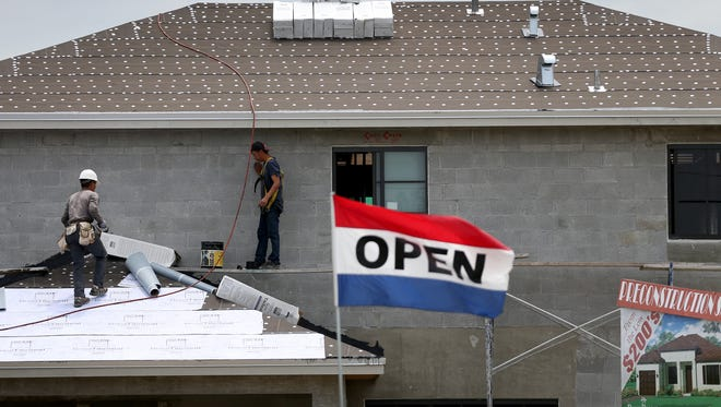 Construction workers work on a new single family home in Miami in April.