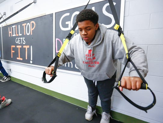 O'Neil Noel, 13, works out during his school day in
