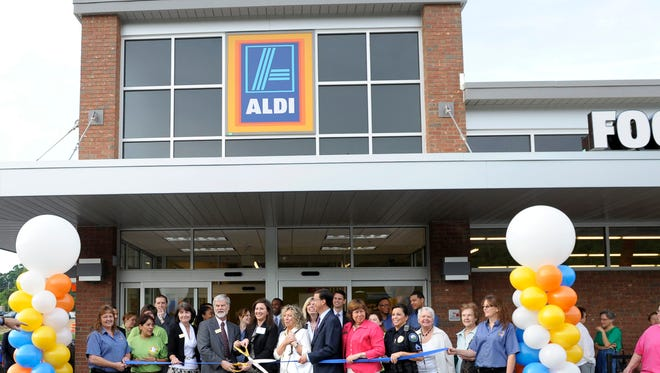 Roswell Mayor Jere Wood, left, counts down to the ribbon cutting, at one of three ALDI grand openings in metro Atlanta.