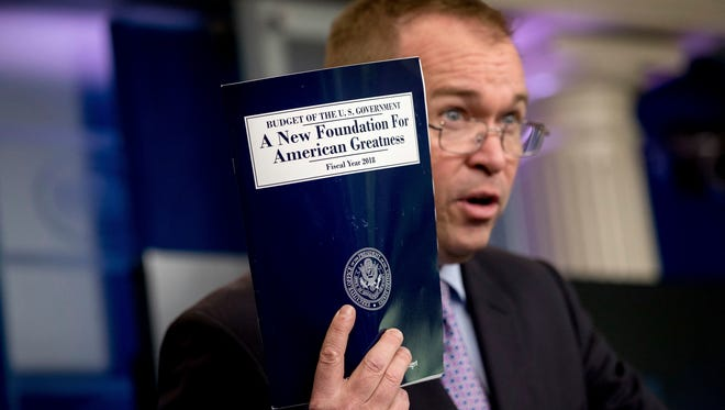 In this May 23, 2017, photo, Budget Director Mick Mulvaney holds up a copy of President Donald Trump's proposed fiscal 2018 federal budget as he speaks to members of the media in the Press Briefing Room of the White House in Washington.