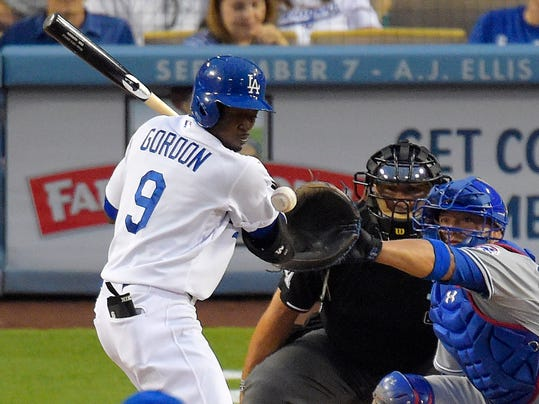 Los Angeles Dodgers' Dee Gordon, left, is hit by a pitch as Chicago Cubs catcher Welington Castillo, right, and home plate umpire Tony Randazzo look on during the fourth inning of a baseball game, Saturday, Aug. 2, 2014, in Los Angeles. (AP Photo/Mark J. Terrill)