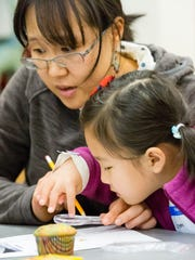 "Gemma Park, 5, and her mother, Jinyoung Kim, look closely at their cupcake excavation samples on Saturday, January 6, 2018, at the Las Cruces Museum of Nature & Science. Participants drilled for the samples using the cupcakes, which represented ice, as they learned about Ice Core excavations during ""Saturday Family Science."""