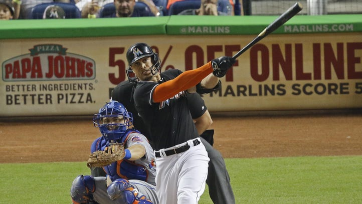 The Marlins' Giancarlo Stanton hits a two-run home run during the third inning in front of Mets catcher Travis d'Arnaud during Miami's 7-2 win over New York on Saturday in Miami.