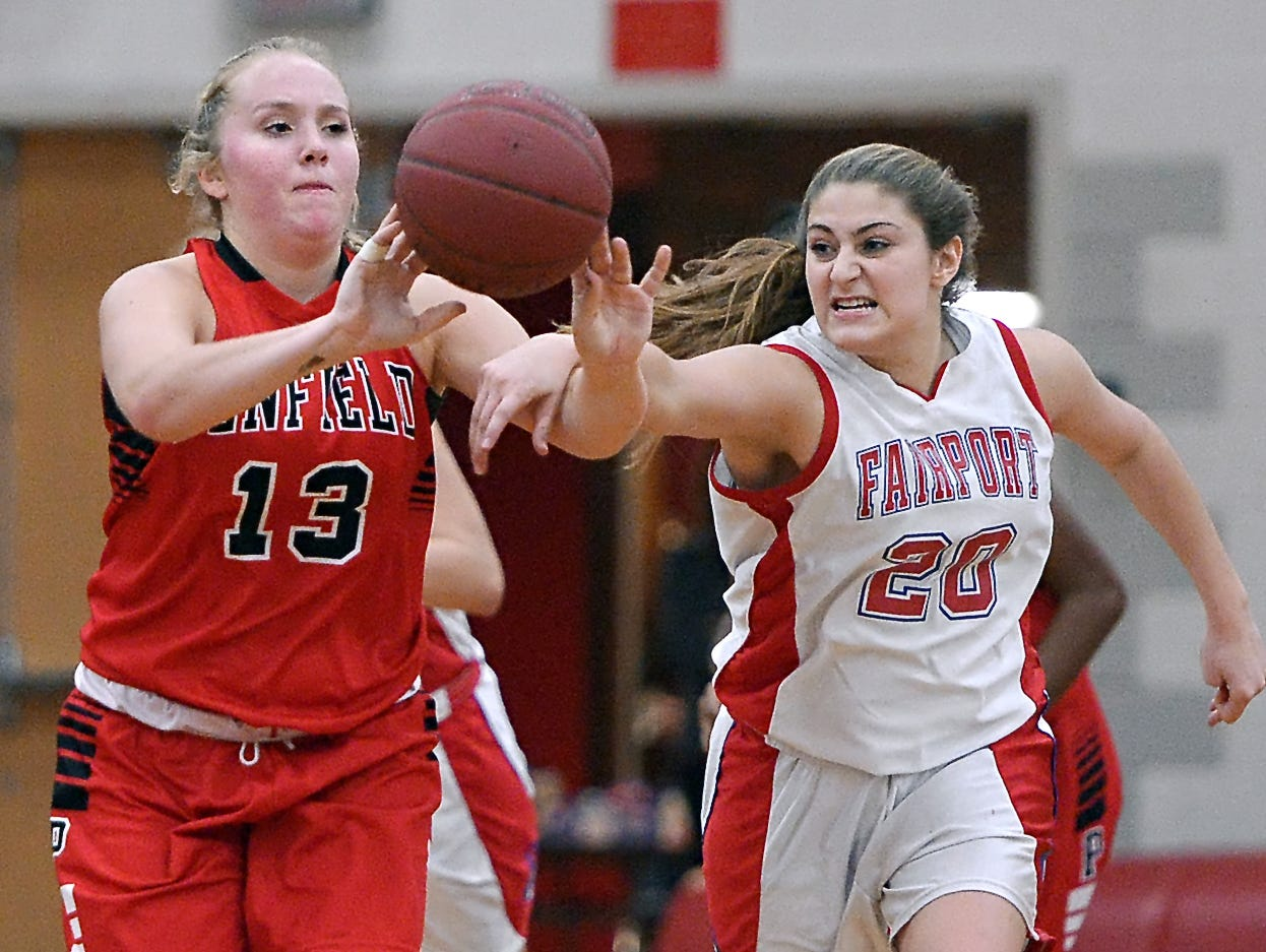 Penfield's Ali Fitzgerald, left, releases a pass while pressured by Fairport's Catherine Tucci.
