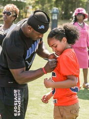 Former Immaculata star Theo Riddick, now an NFL running back with the Detroit Lions, signs a jersey for cousin Tarae Jackson of Somerville. Riddick was in Somerville for a dedication to change the name of the school's football field to Riddick Field on June 27, 2016.