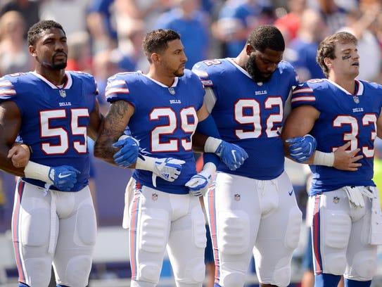 Buffalo Bills players listen to the national anthem