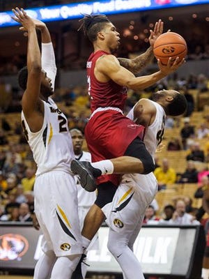 Western Kentucky's Pancake Thomas, center, shoots between Missouri's Kevin Puryear, left, and Russell Woods, right, during the second half of an NCAA college basketball game Saturday, Dec. 3, 2016, in Columbia, Mo. Missouri won the game 59-56. (AP Photo/L.G. Patterson)