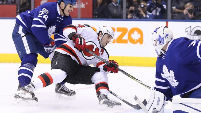 Devils center Adam Henrique (14) draws a penalty as he is hooked from behind by Toronto Maple Leafs center Brian Boyle (24) at Air Canada Centre in Toronto on Thursday night.