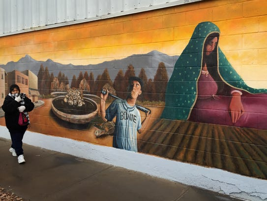 A woman walks past a mural of the Virgin of Guadalupe