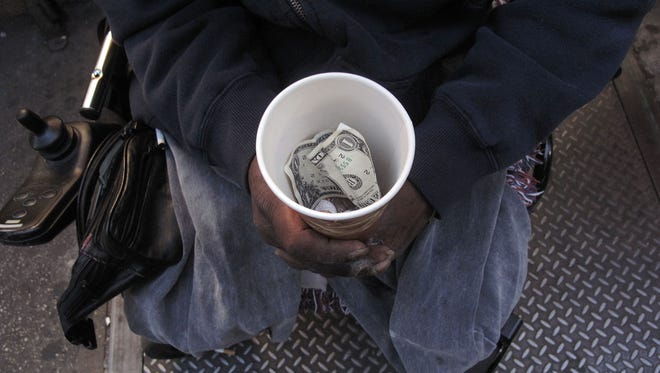 A homeless man displays a cup containing money from panhandling.