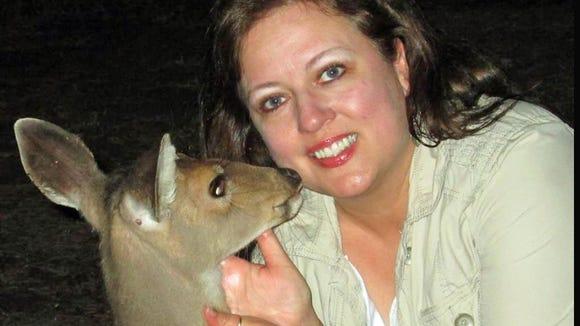 "Susan Miller pets an affectionate ""Frank,"" a deer she helped rescue."