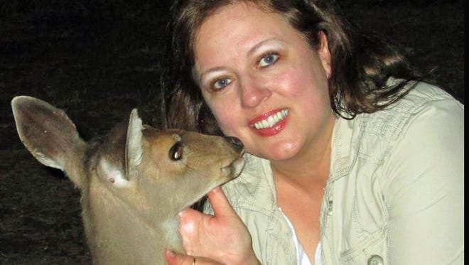"Susan Miller pets an affectionate ""Frank,"" a deer she helped rescue."