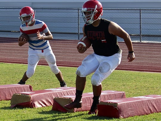 Two Desert Mirage High School football players do footwork drills to improve their agility during a training session at the Rams' practice field on Aug. 13, 2015.